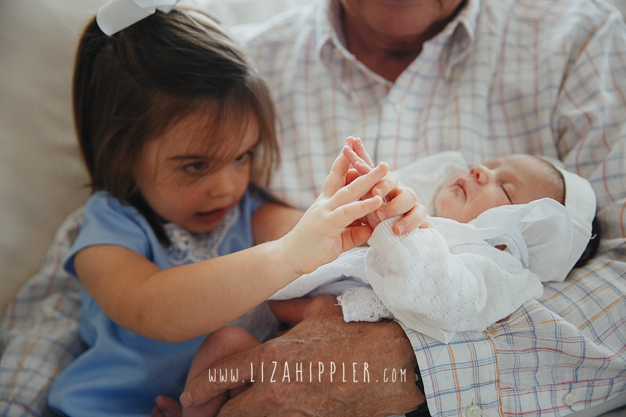 big sister and newborn sister hold hands