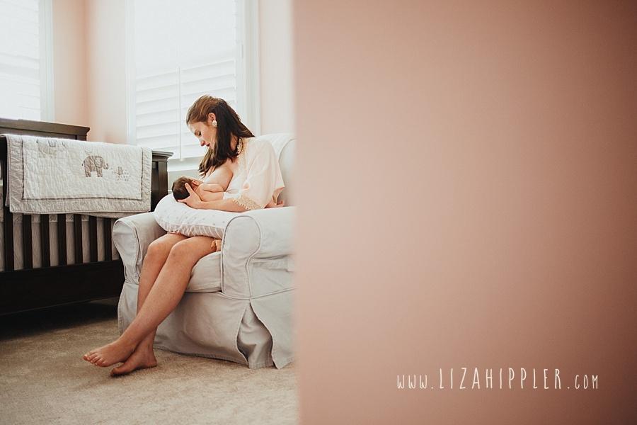 mom nurses newborn girl in pink nursery