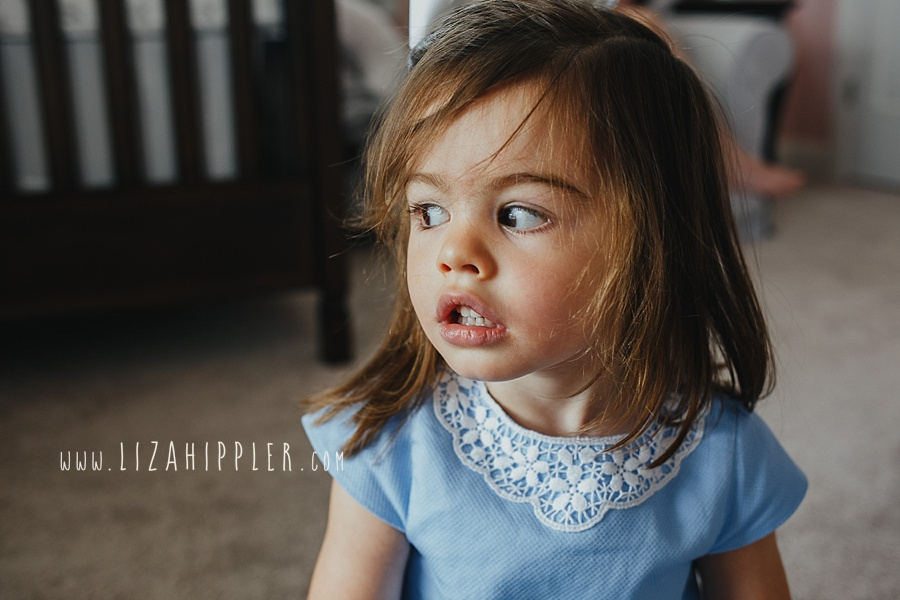 adorable toddler girl in blue dress looks out window