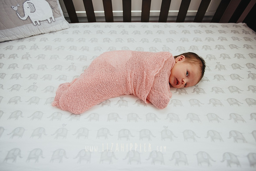 newborn girl swaddled in pink in brown crib