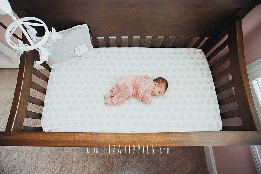 newborn girl in pink blanket laying in brown crib