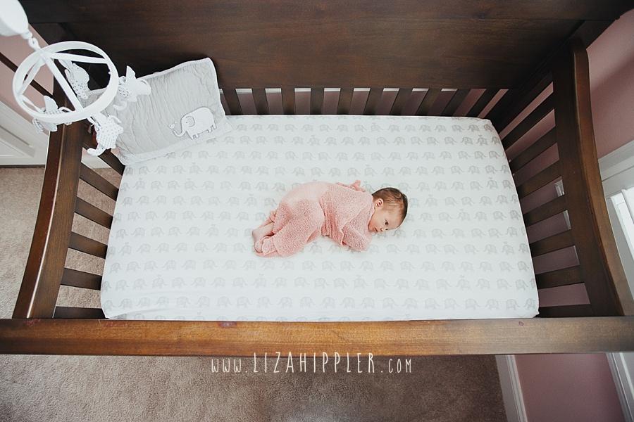newborn girl in pink blanket laying in brown crib