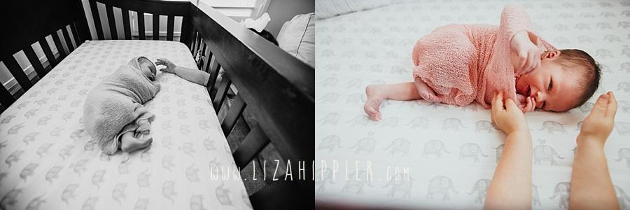 big sister reaches for newborn sister through crib
