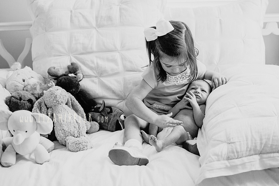 big sister touches newborn sister's toes