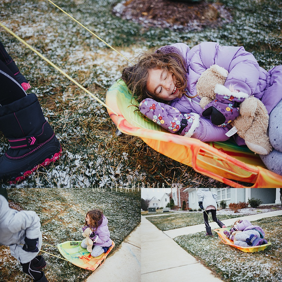 girl lies down on sled in purple coat