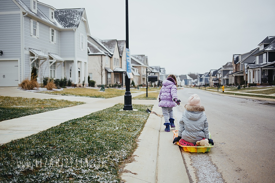 little sister pulls big sister on sled down the street