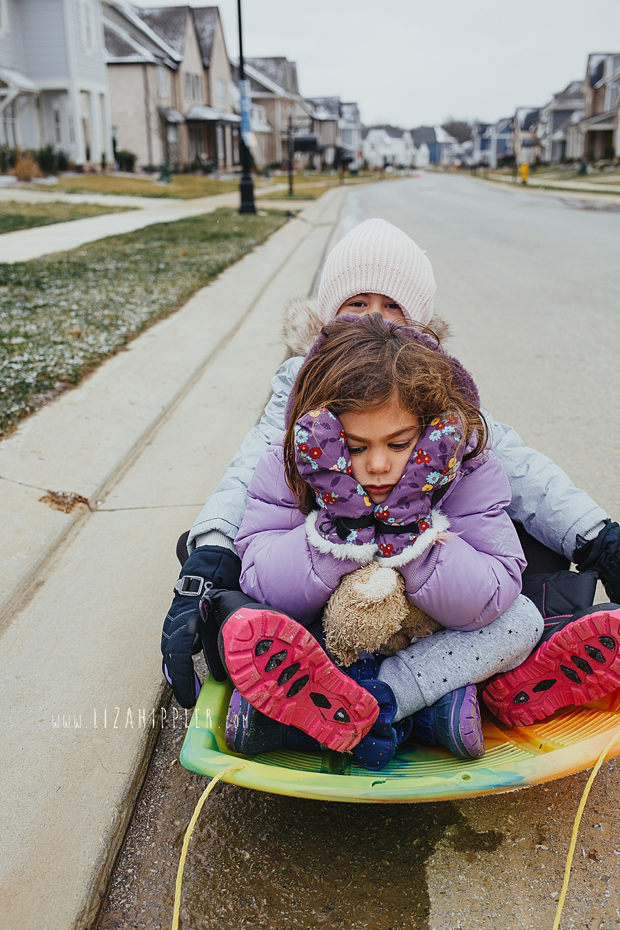 sisters sitting on sled together while one gives a pouty face