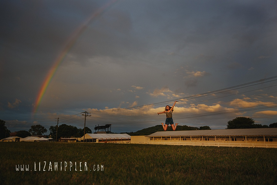 high school senior girl jumps up under rainbow and clouds