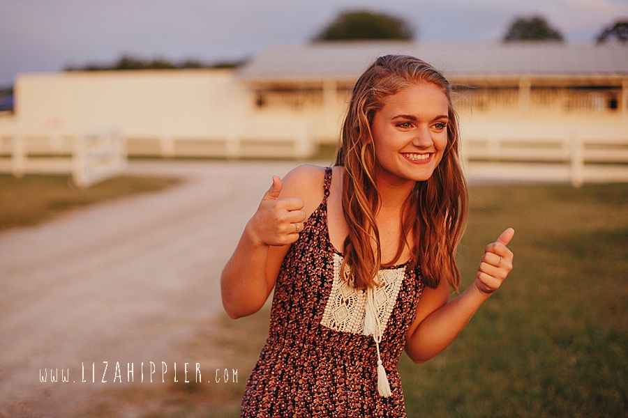 high school senior gives thumbs up during her photo shoot
