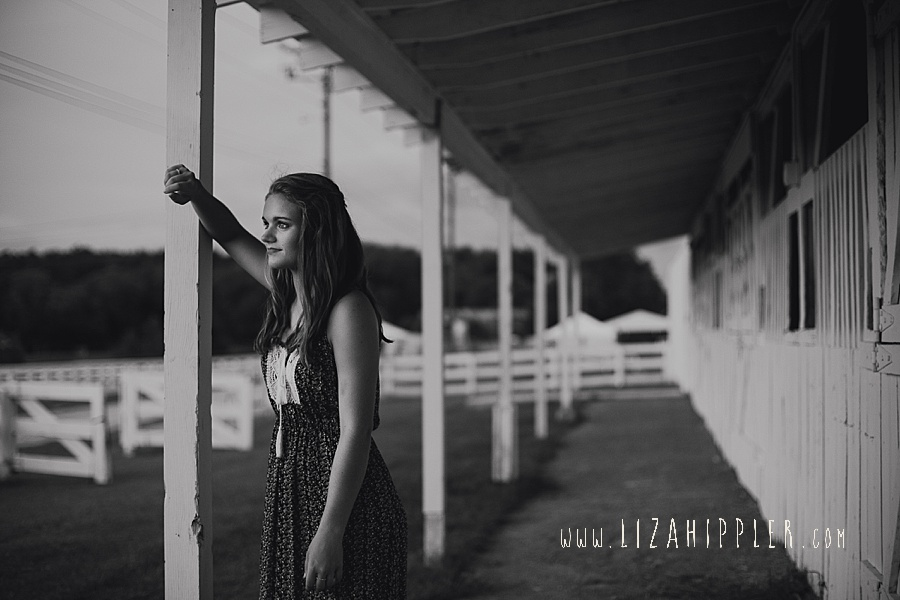 black and white photo of high school senior looking out at sunset from harlinsdale farm stables