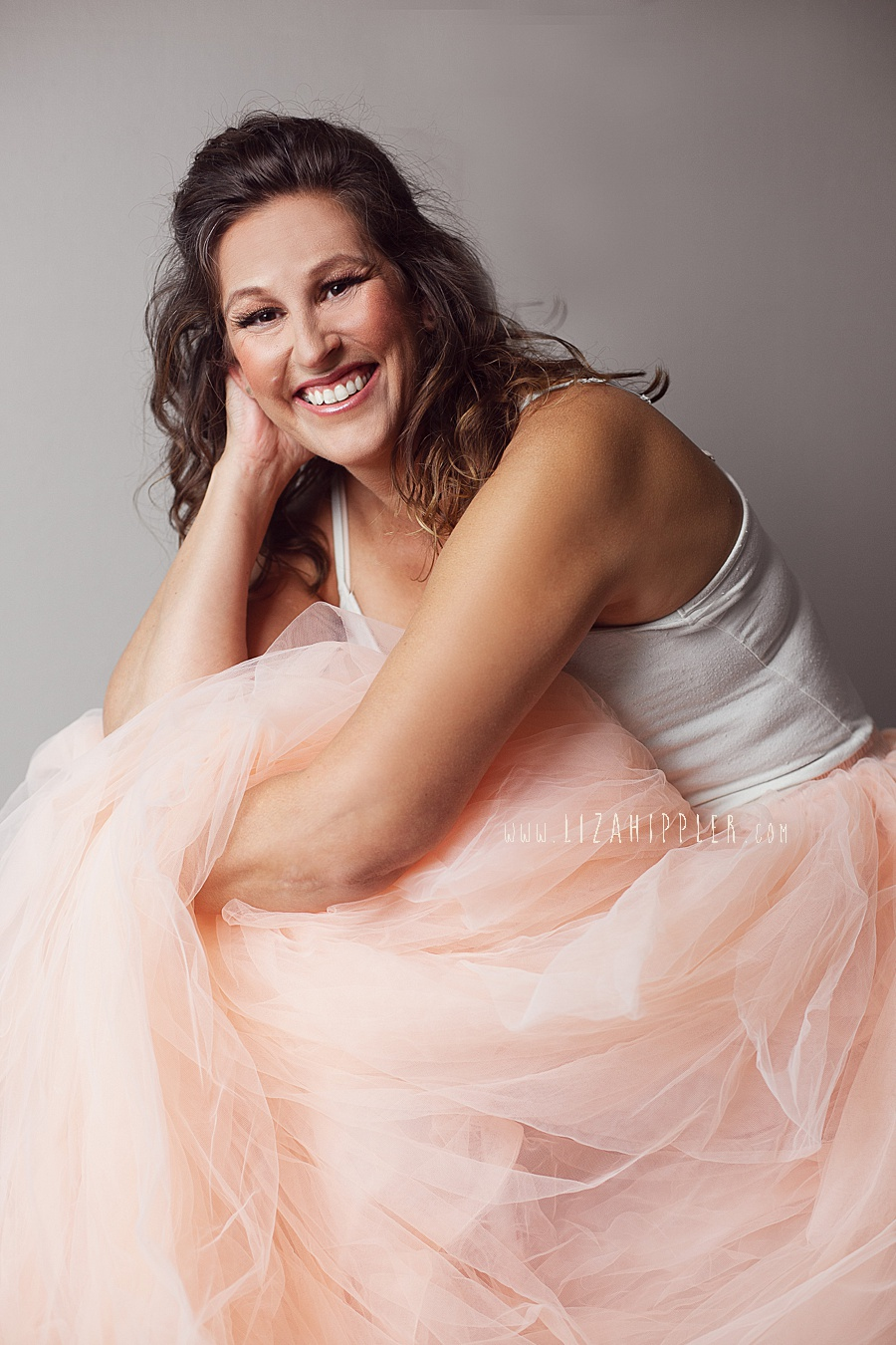 brunette woman in pink tulle skirt on grey background