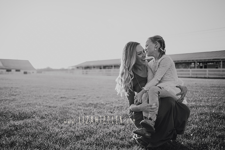 young daughter whispers in mom's ear black and white