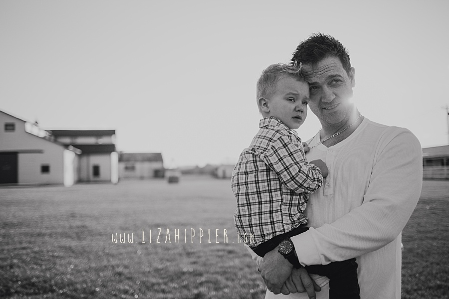 dad and toddler sun look off with barn in background