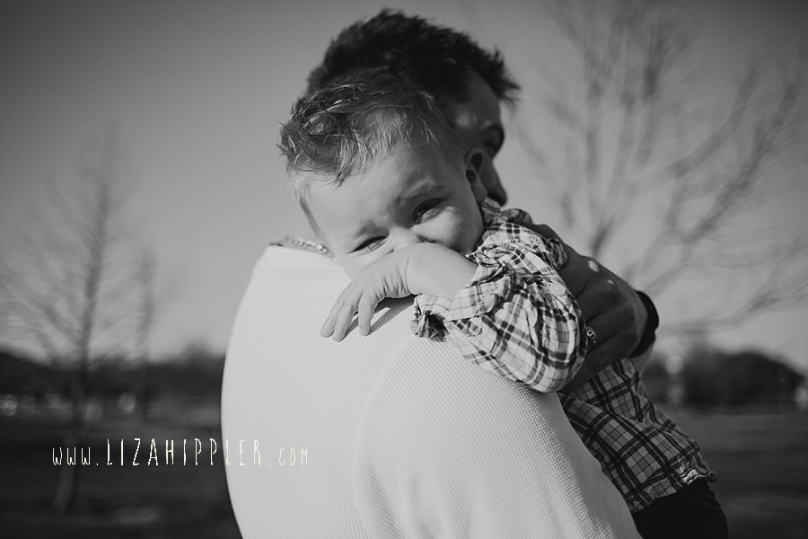 toddler son snuggles over dad's shoulder black and white