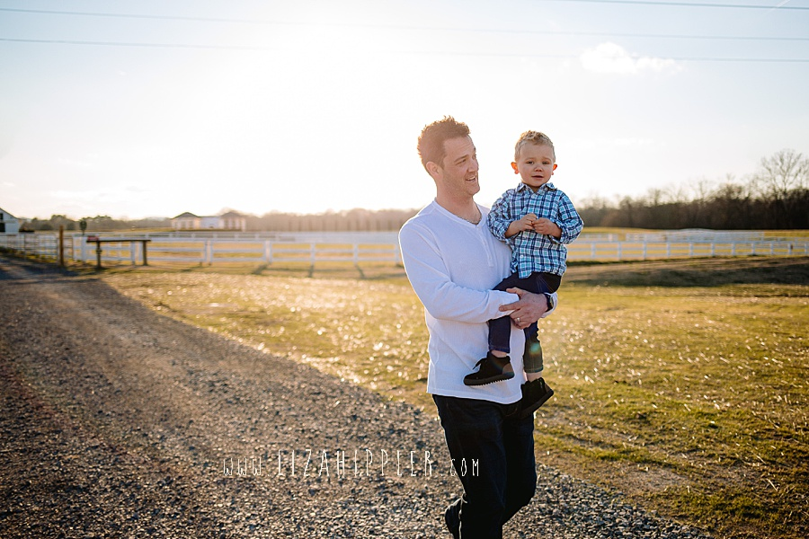dad walks down dirt path with toddler son in blue plaid