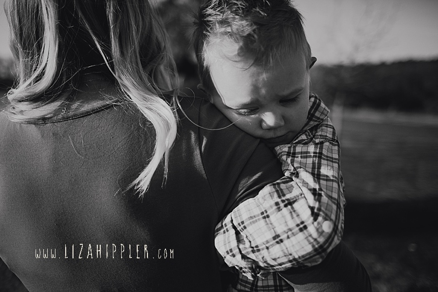 black and white of toddler boy snuggling on mom's arm