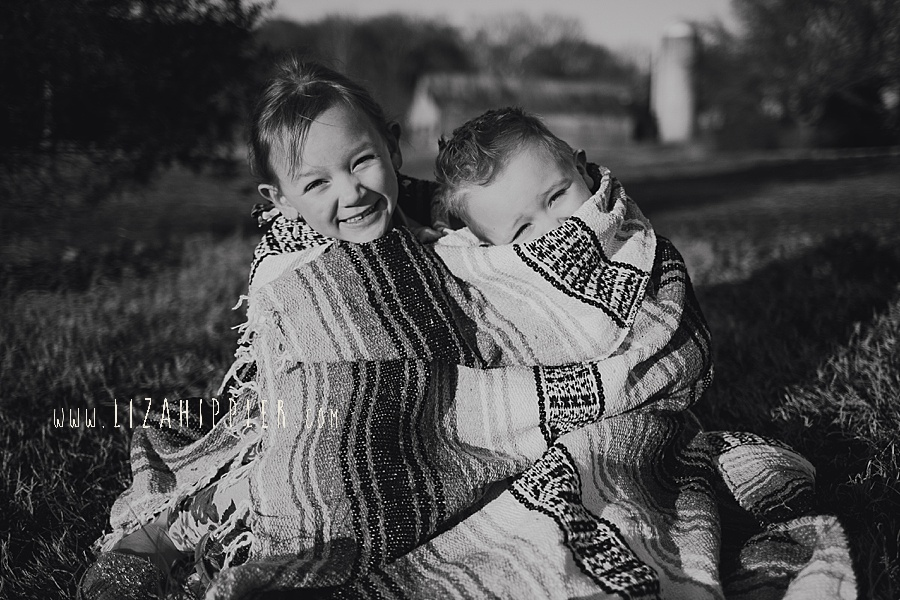 black and white of young siblings snuggling under blanket outside being silly