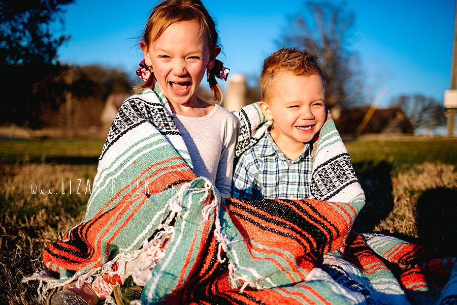 siblings popping out of mexican blanket outside