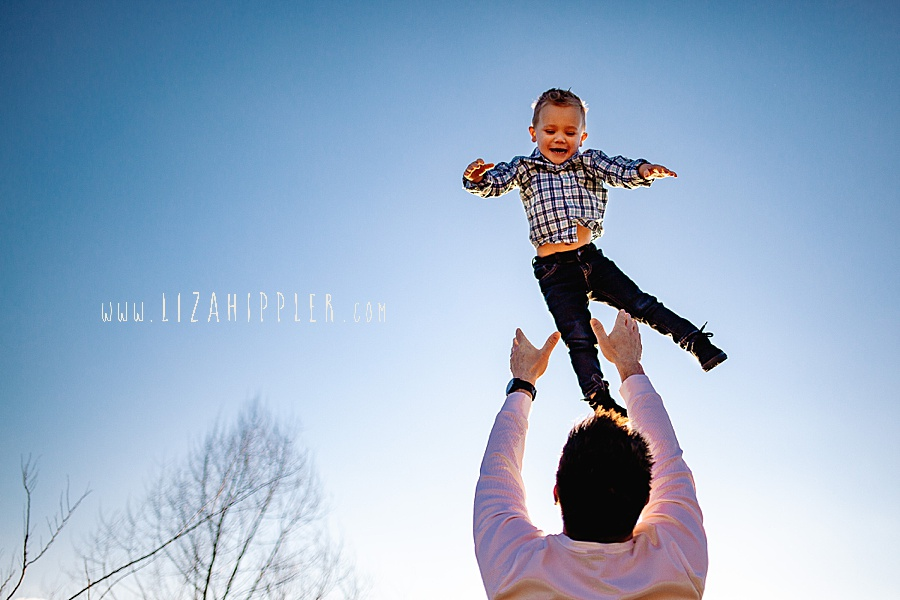 toddler boy gets tossed high into the air by his dad