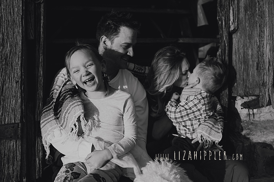 black and white photo of family snuggling in barn