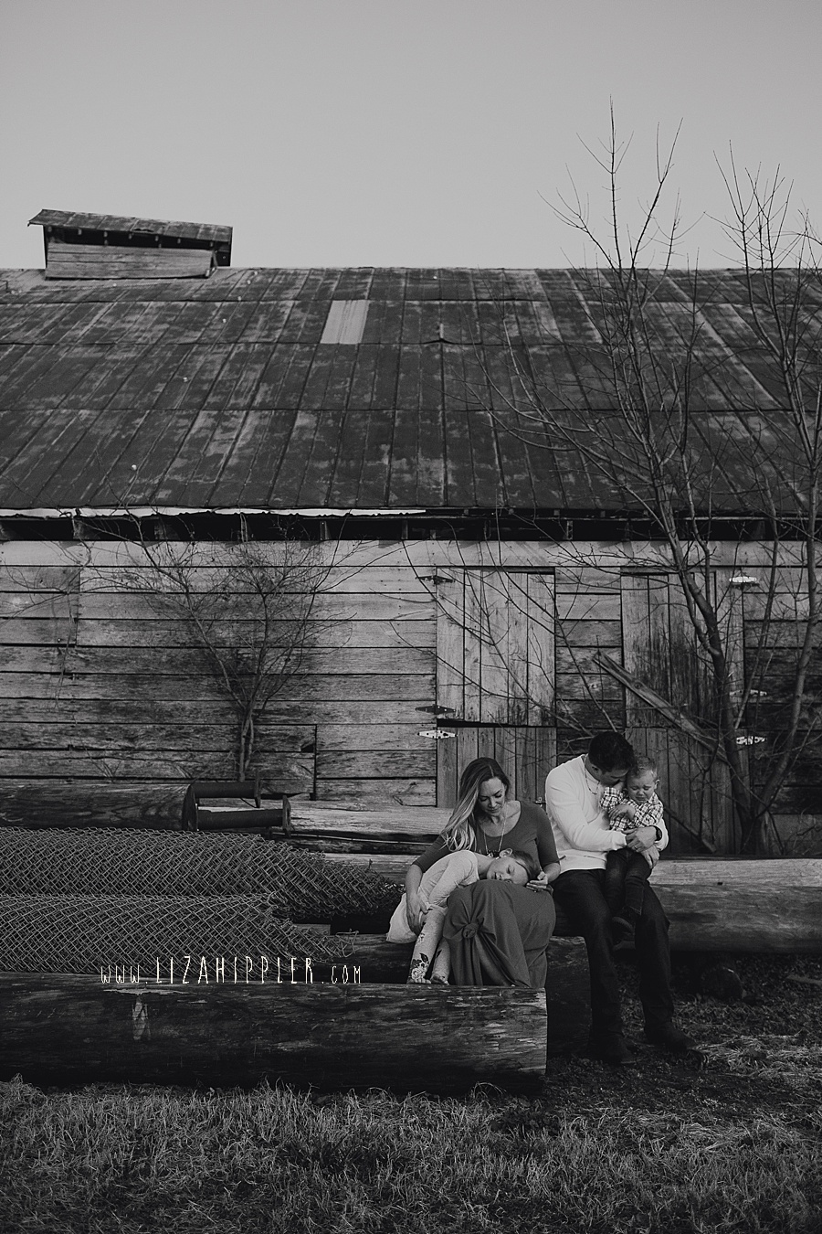 black and white image of family sitting in front of a barn