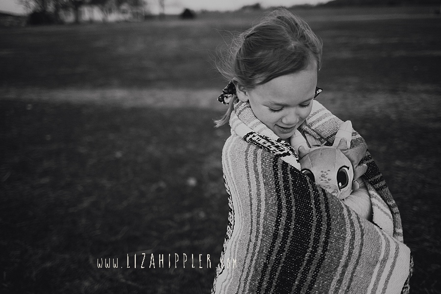 young girl walks in the cold with blanket and snuggles with her stuffed animal