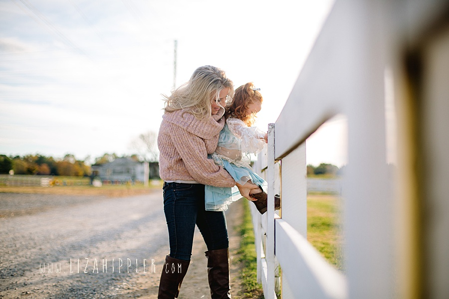 blonde mom helps her toddler girl climb a fence