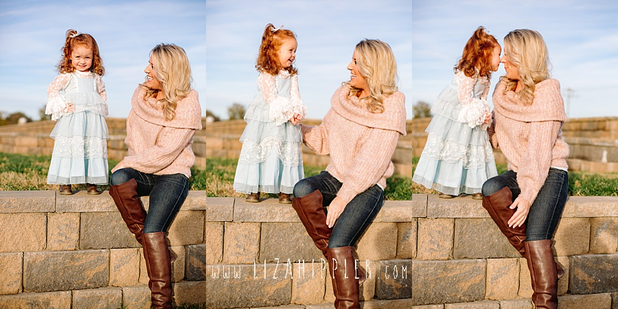 blonde mom sits on stone wall while talking to toddler daughter