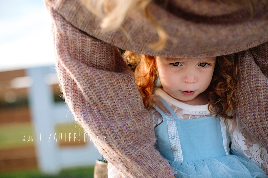 daughter looks out from under mom's sweater