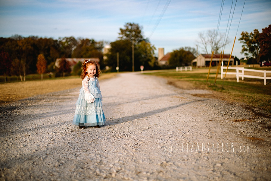 redhead toddler in blue dress stands on dirt road