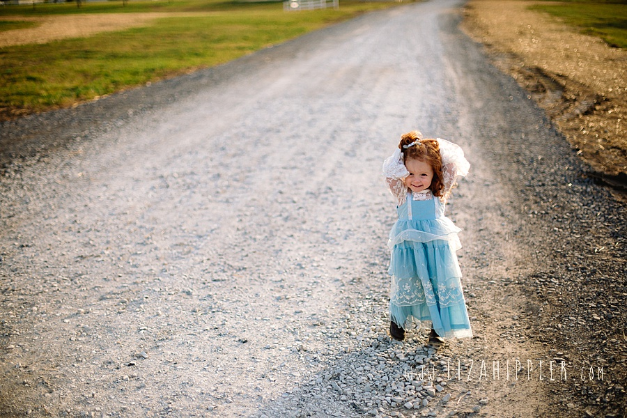 curly redhead little girl is super cute on dirt road