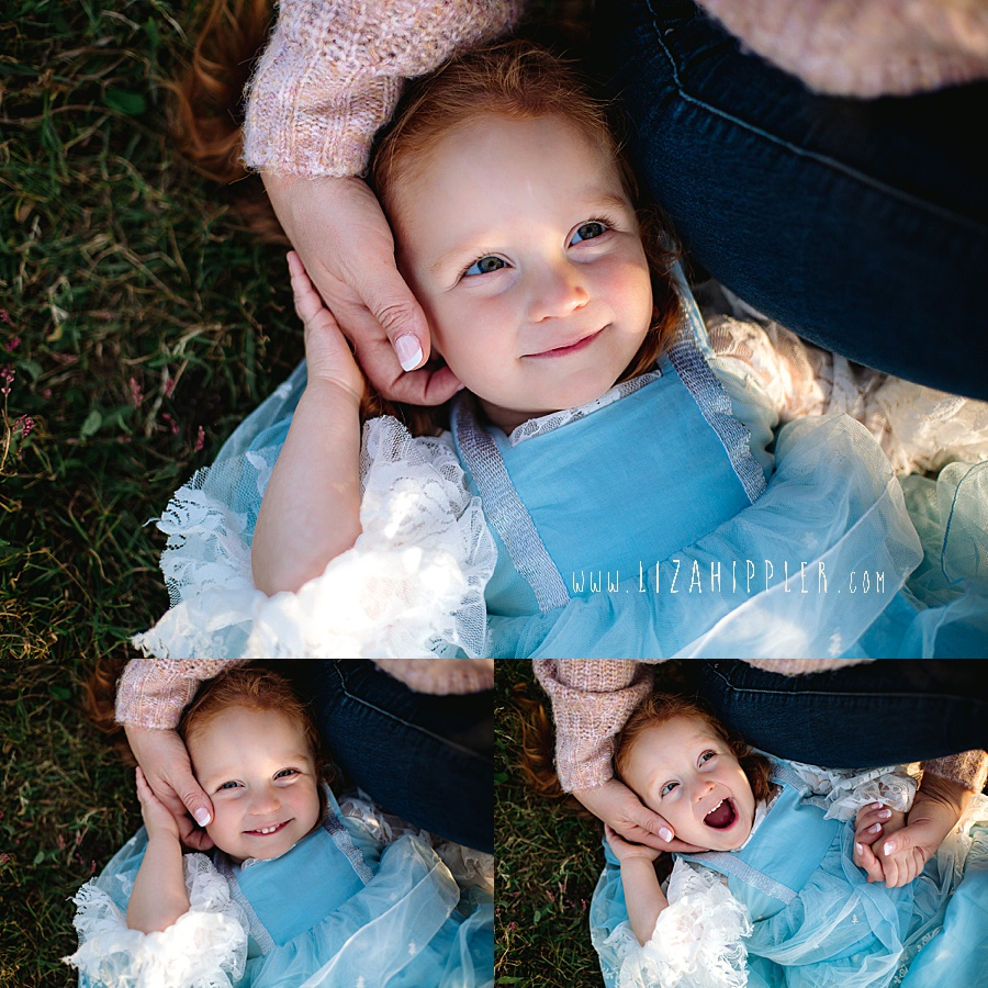 little girl snuggles by mommy's side in the grass