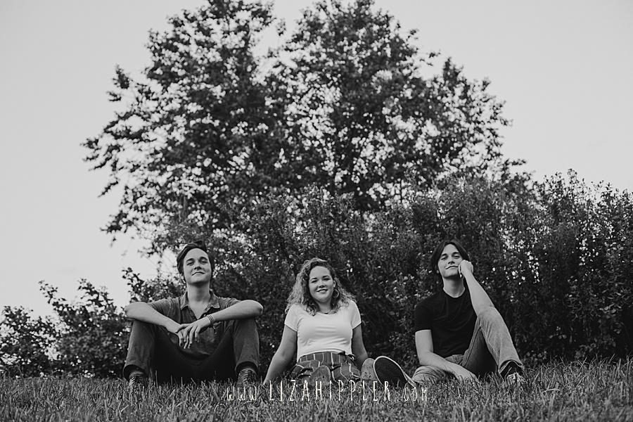 high school senior triplets sit on the grass black and white image