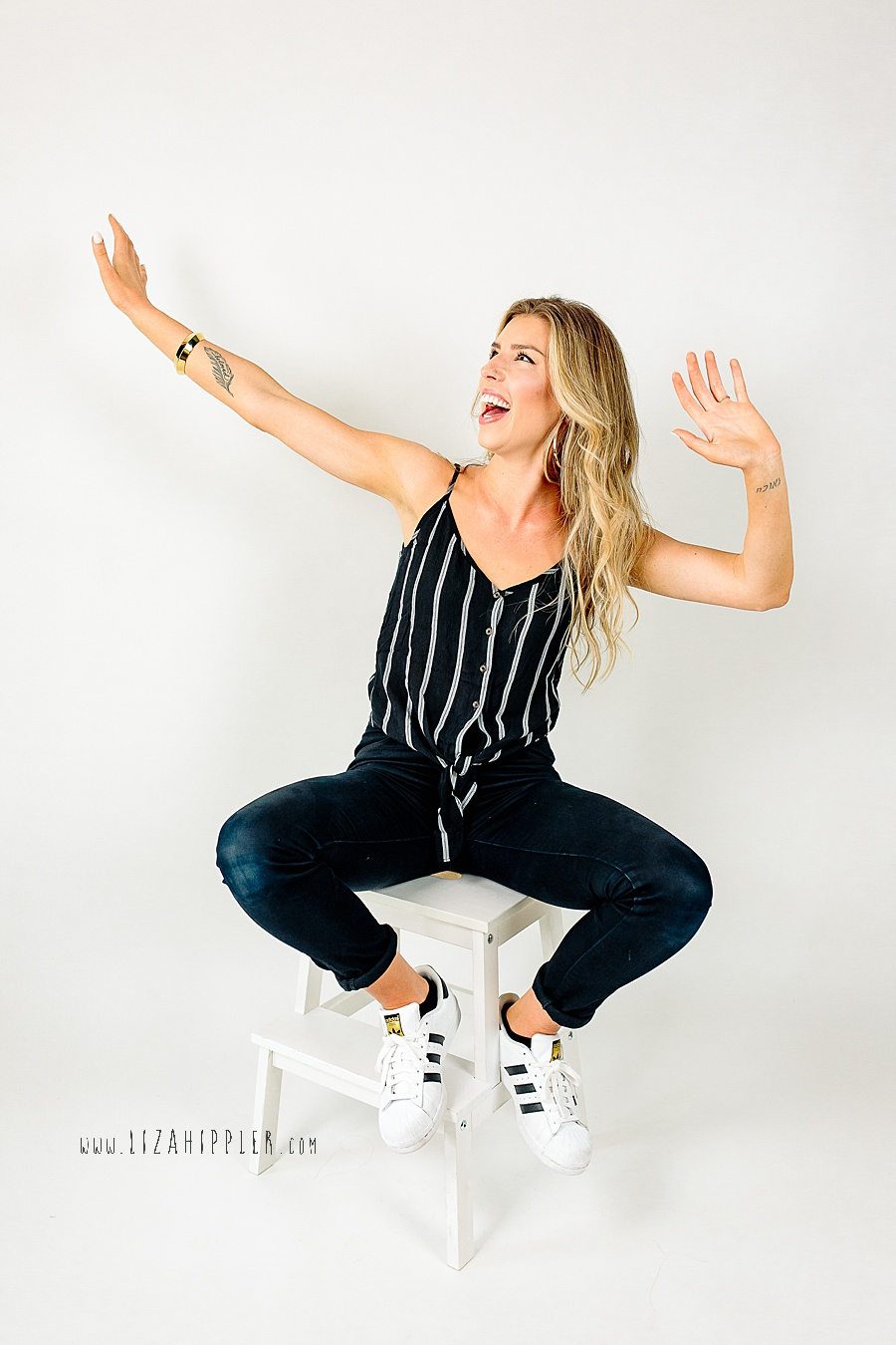 fun headshot of blonde chick doing the dab on a white background
