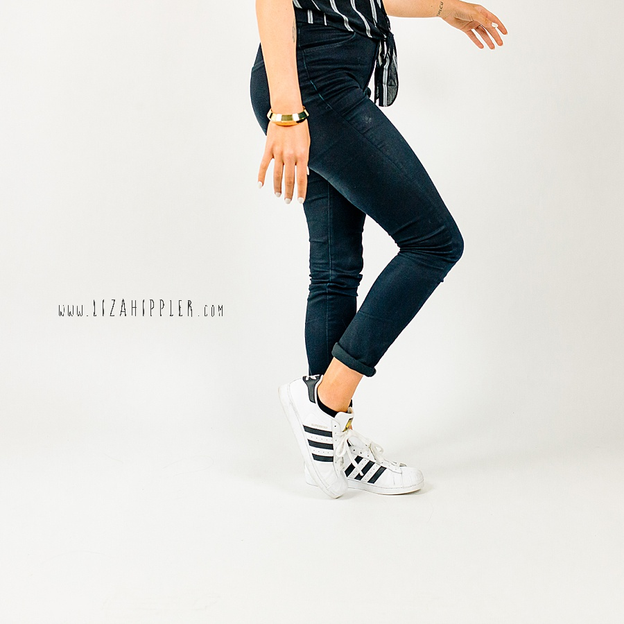 branding photo of woman walking with black jeans and adidas shoes on white background