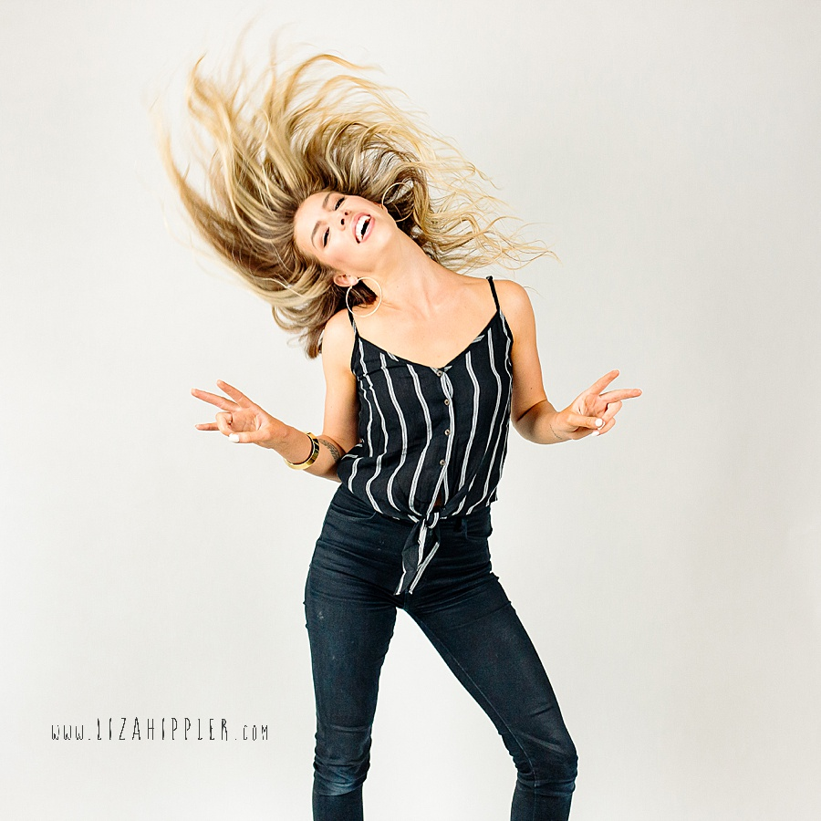 blonde woman with long hair flips it in the air