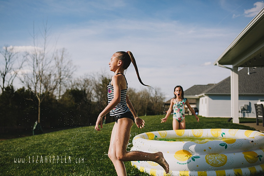 sisters play in lemon pool in backyard