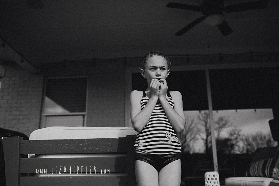 young girl stands in bathing suit black and white