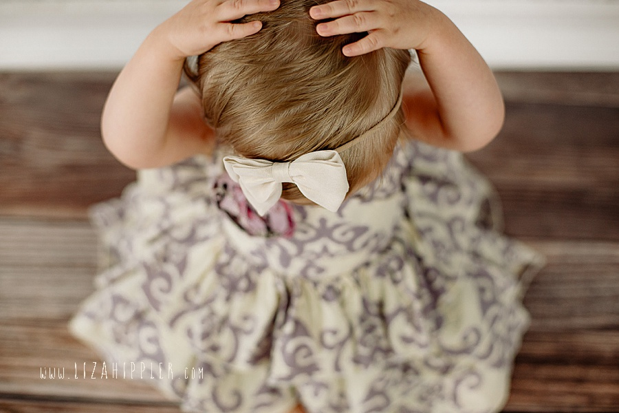 one year old girl tries to take off her bow