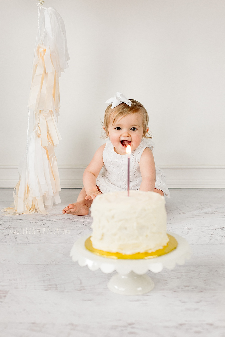 one year old girl gets happy about her birthday cake