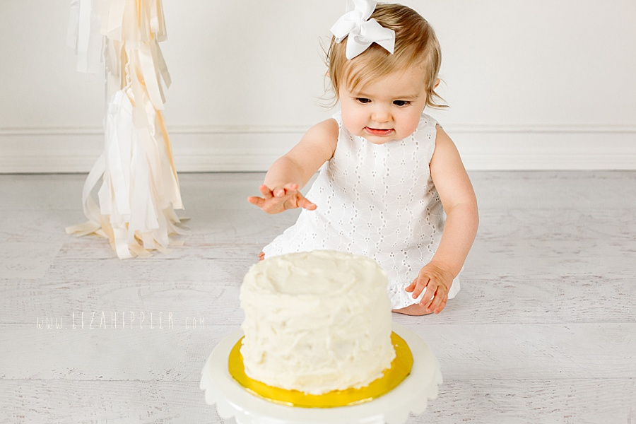 one year old girl about to touch her smash cake