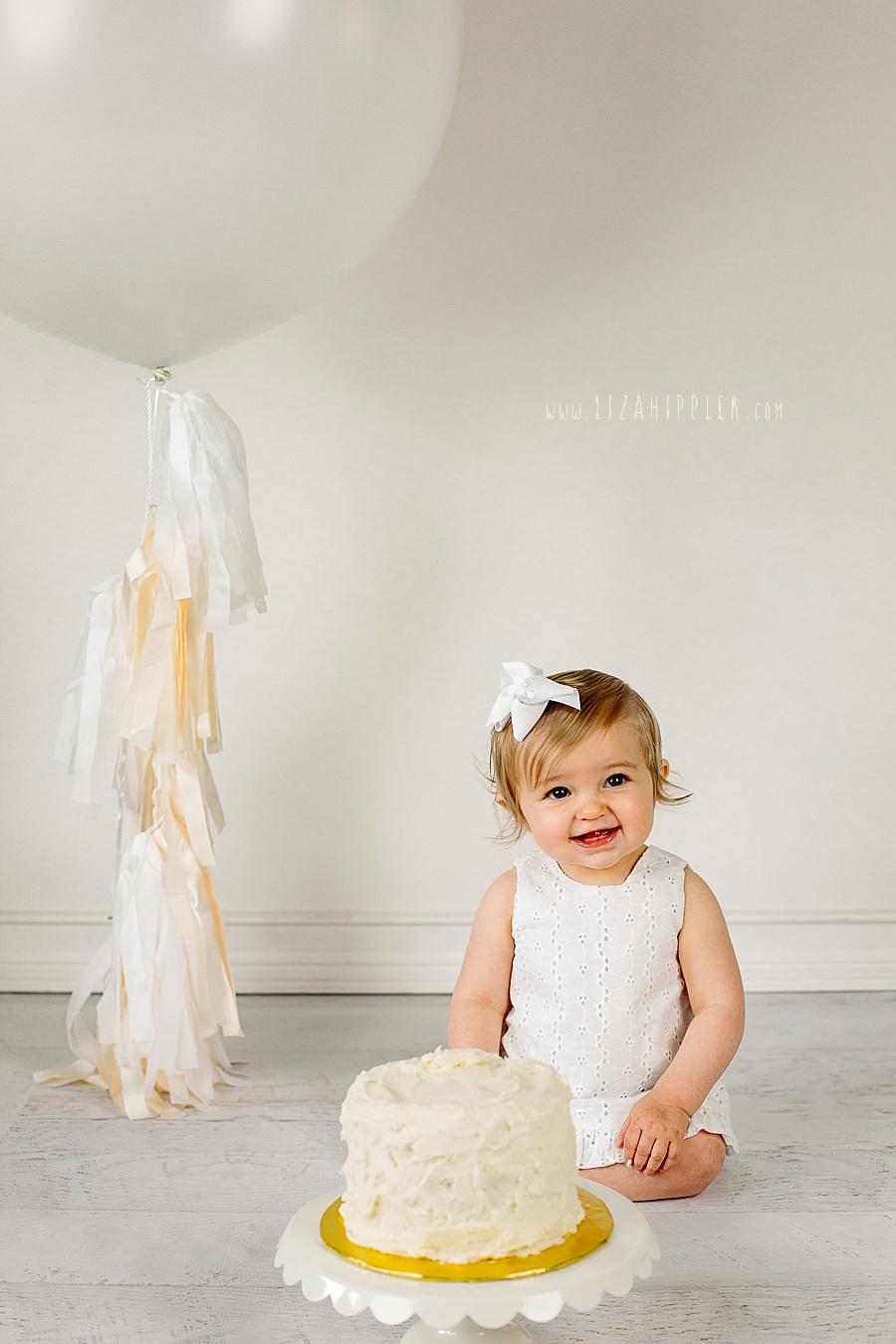 happy first birthday girl in white eyelet dress