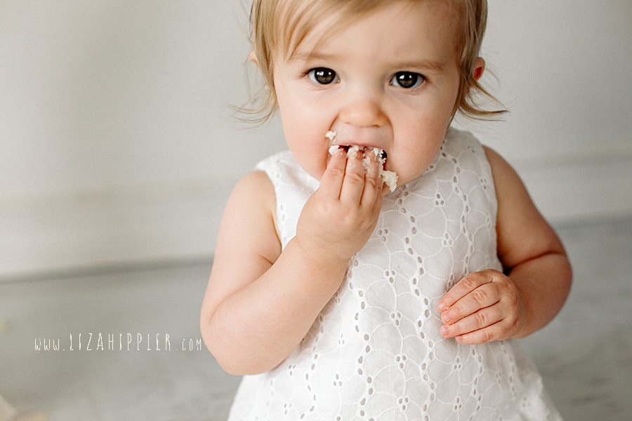 one year old girl put vanilla cake in her mouth