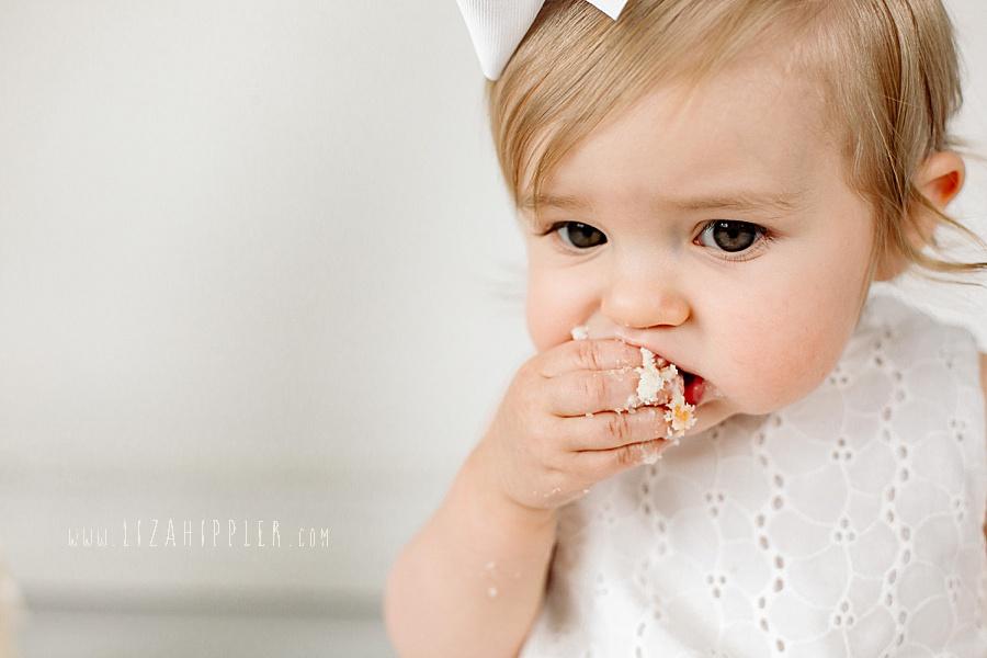 chunky cheek girl tastes cake on first birthday
