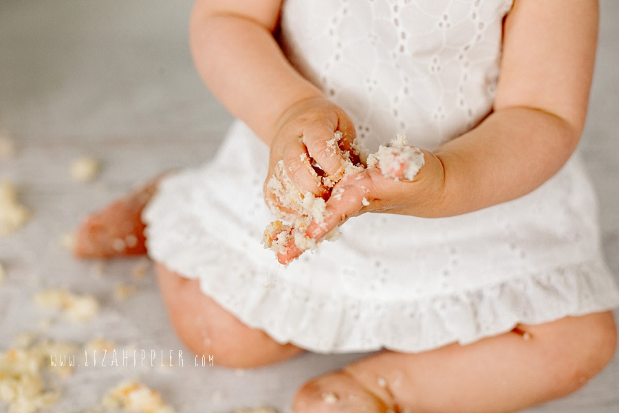 girl on first birthday with hands covered in cake