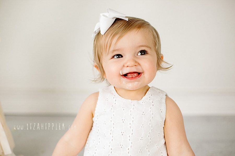 girl smiles big after trying cake on her first birthday
