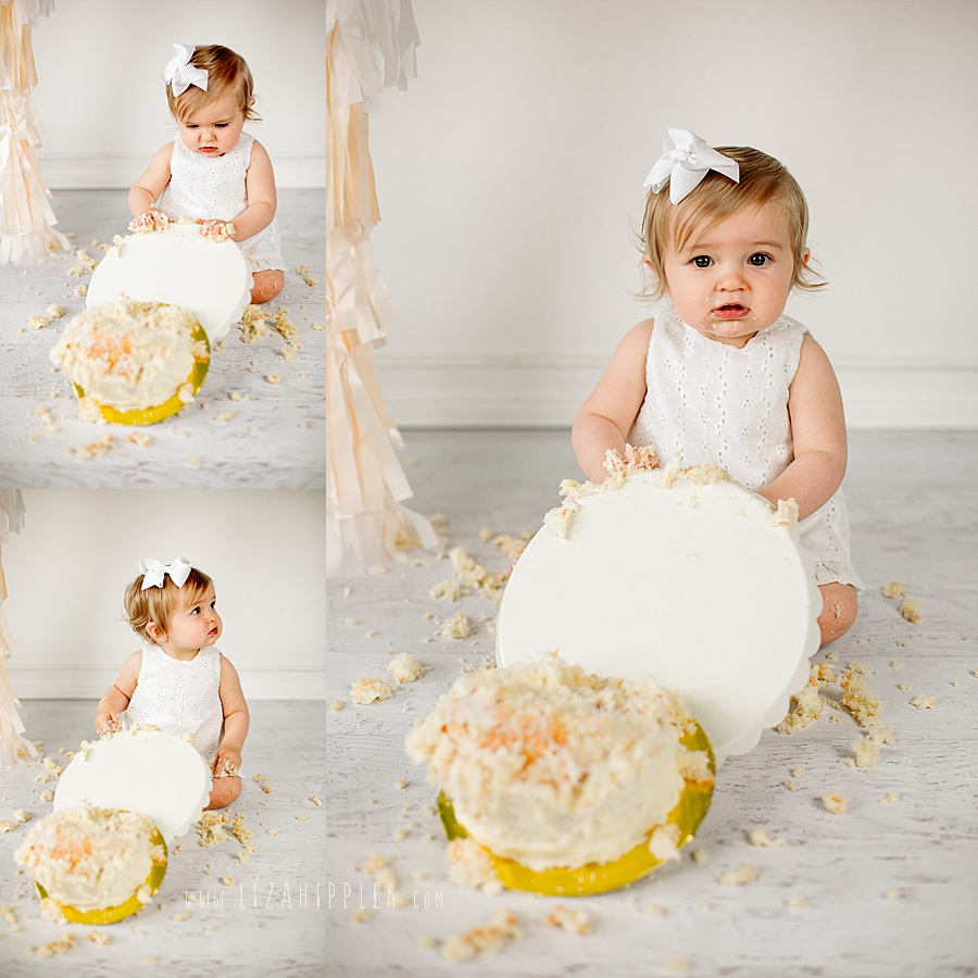 one year old girl tips over cake stand during cake smash session