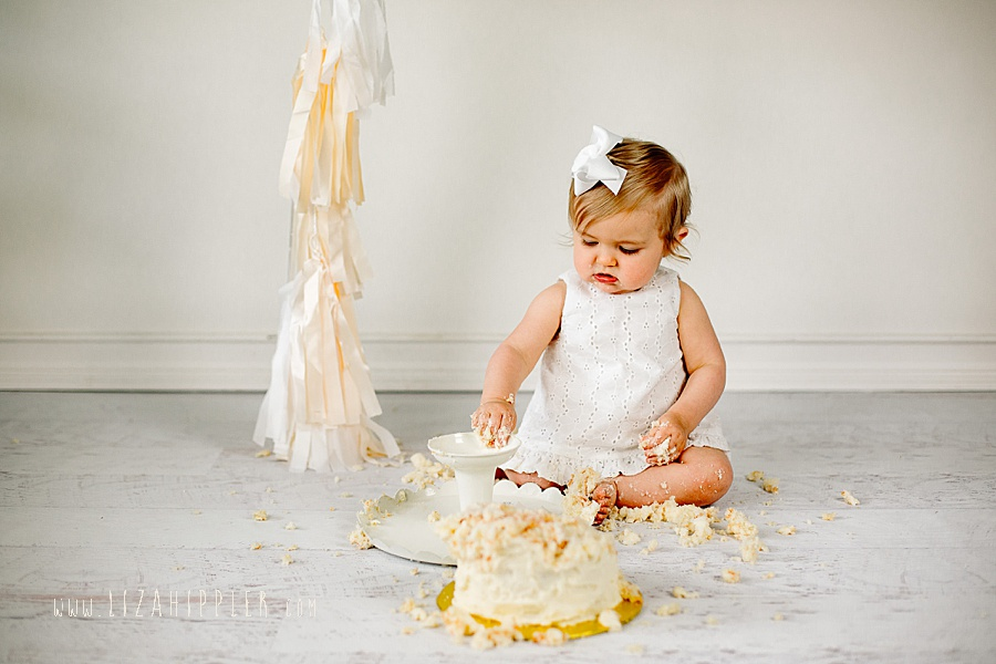 first birthday girl in white dress white backgroun