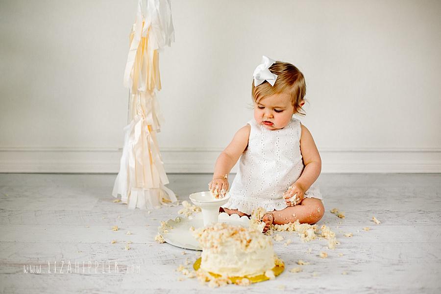 first birthday girl in white dress white backgroun
