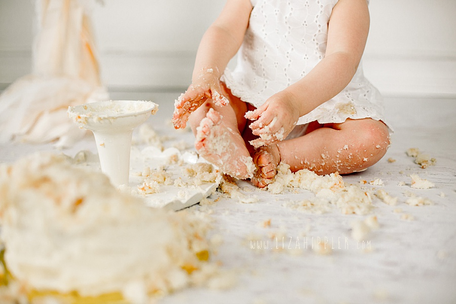 little one year old girl covered in vanilla cake for first birthday
